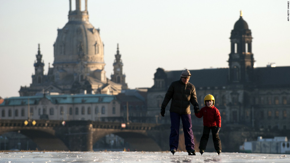 A boy and his mother skate on the partly frozen Elbe River on Thursday as the skyline of Dresden, Germany, is silhouetted in the background.