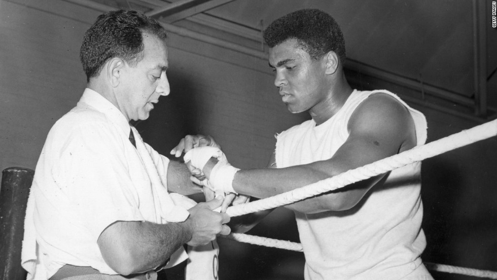 Angelo Dundee helped a young Cassius Clay transform himself into the world heavyweight champion. Here he tapes the renamed Muhammad Ali's hands at a training session ahead of a 1966 bout with British champion Henry Cooper.
