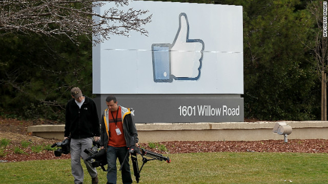 A TV crew carries gear near a sign marking Facebook's headquarters in Menlo Park, California.