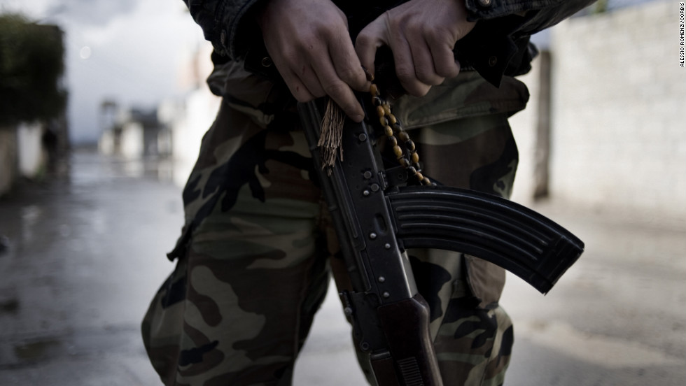 A member of the Free Syrian Army holds an AK-47 and prayer beads in the streets of Al-Qusayr.