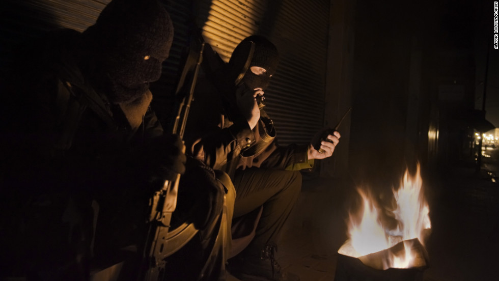 Free Syrian Army fighters stand guard at night in Al- Qusayr. The humanitarian crisis in Syria continues to worsen as armed rebels and government forces battle for control of towns and cities across the country.