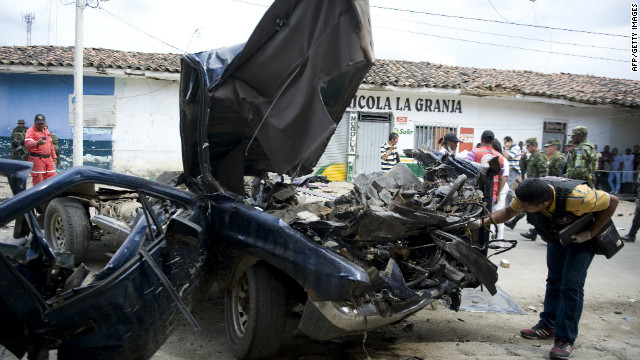 member of the Colombian Technical Investigation Team (CTI in Spanish) inspects the remains of the vehicle from which a cylinder bomb was launched against the National Police headquarters on February 2, 2012