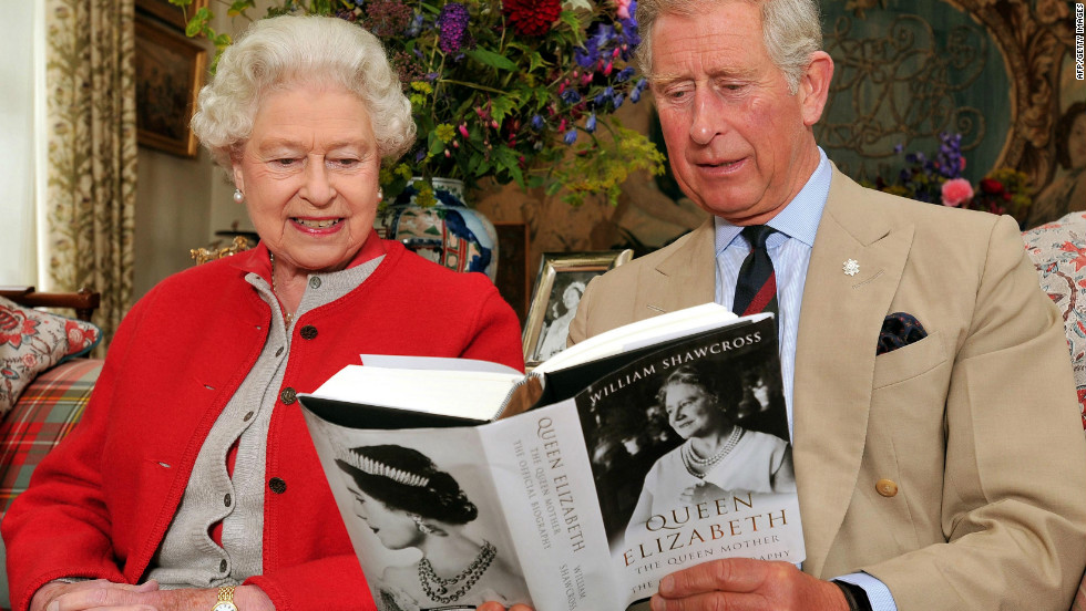 September 2, 2009: Queen Elizabeth II sits with the Prince Charles, and studies one of the first copies of ' Queen Elizabeth The Queen Mother, The Official Biography' in a living room at Birkhall the Scottish home of the Prince and Duchess of Cornwall.