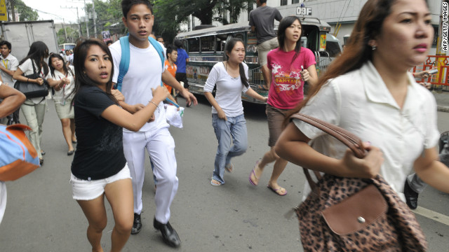 Residents scamper to safety after a 6.8 earthquake hit near Cebu City on Monday.