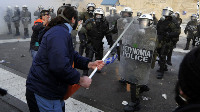 Protesters clash with riot police in front of the Greek Parliament in Athens on February 12, 2012.