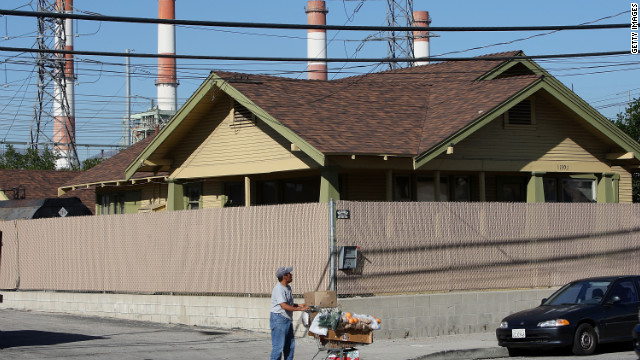 A fruit vendor walks near the Department of Water and Power San Fernando Valley Generating Station  in Sun Valley, California.