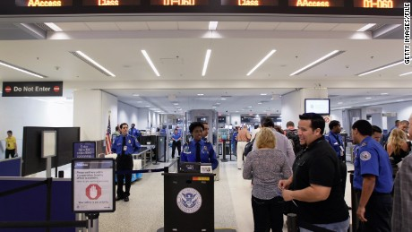Passengers wait to be screened at a security checkpoint at Miami International Airport.