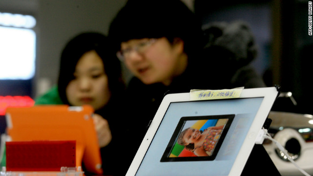 Two customers check out an ipad with a note attached that reads 'Display as a sample, not for sale' at a computer shop in Dalian, northeast China's Liaoning province on February 13