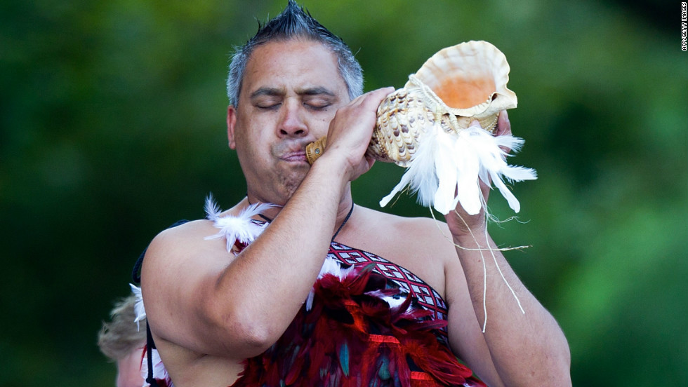 A Maori warrior blows a putatara shell during a quake remembrance service in Hagley Park, Christchurch.