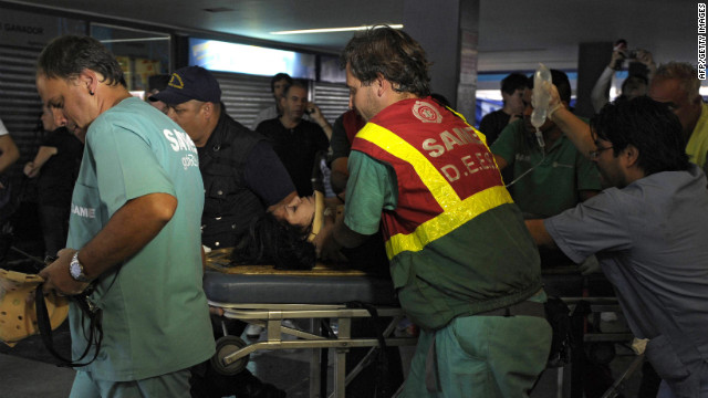 Police and rescue workers transport an injured woman on a stretcher after a train crashed at Once train station in Buenos Aires on February 22, 2012