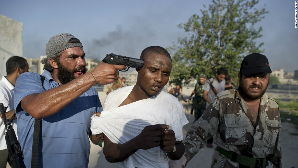 His work was published in Time, Paris Match, Le Monde and the Wall Street Journal.Photo: Rebel fighters in Tripoli, Libya, captured Africans they accused of being Gadhafi mercenaries.