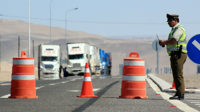 Police stop traffic at the Chile-Peru border after rain washed landmines onto the highway, February 21, 2012.