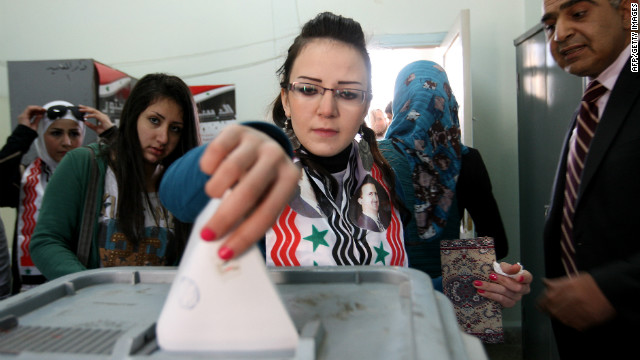 A Syrian woman wearing a scarf with pictures of Syrian President Bashar al-Assad casts her vote on a new constitution at a polling station in Damascus on February 26.