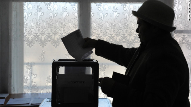 A woman casts her ballot at a polling station on February 26, 2012, during a pre-term voting for Russia's presidential elections.