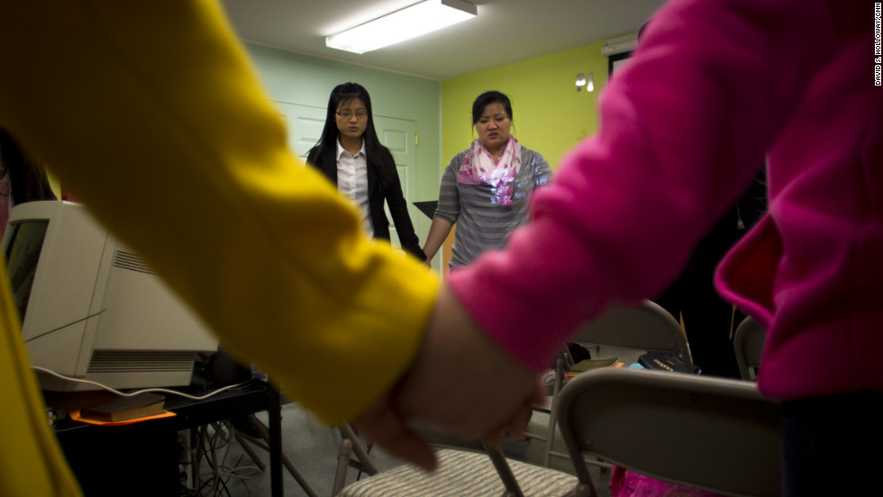 Han's two daughters, EunHye, 20, and JinHye, 24, pray at the Pilgrim Community Church in Virginia. In 1998, the sisters, severely malnourished, walked for three days and crossed the Tumen River to escape into China. They had to leave their younger brother behind in North Korea.