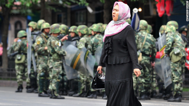 A Uighur woman crosses a street in front of Chinese soldiers in Urumqi in this file picture dated July 15, 2009