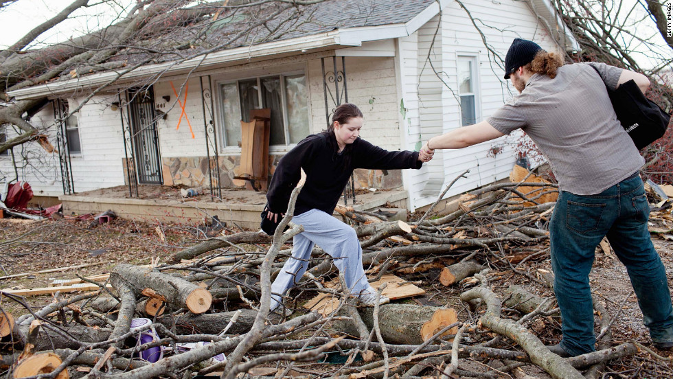 Levi Fogle helps girlfriend Sarah Pearce leave a damaged house in Harrisburg. Fogle, Pearce and her three daughters went unharmed in the storm.