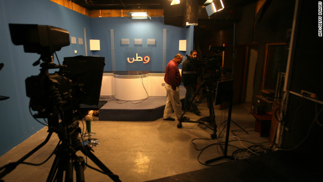 "Employees walk through a studio at Palestinian television station ""Wattan"" after Israeli troops raided the station overnight."