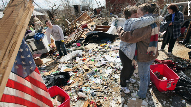 Melody Zollman, left, hugs sister Michelle Browning in what is left of Zollman's home after a tornado in Henryville, Indiana.