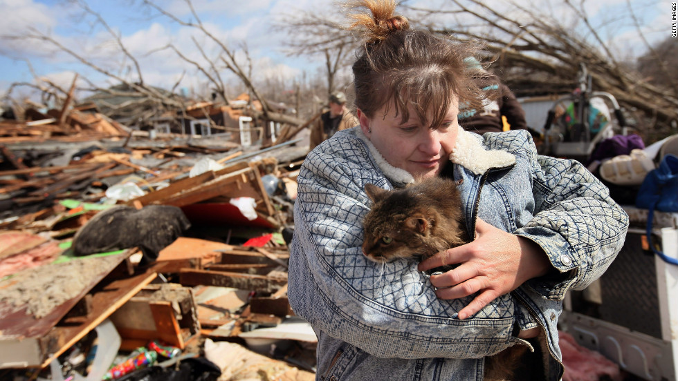 Zollman hugs her cat Thumbelina after it was pulled from the debris of her home.
