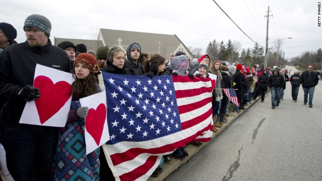 People stand along the road in Chardon, Ohio, before the funeral for 16-year-old Danny Parmertor.