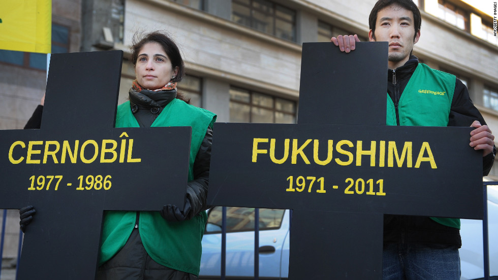 "Greenpeace activists hold black crosses. one reading ""Fukushima"" nuclear power plant and the other, ""Chernobyl,"" at a protest in Bucharest March 5."