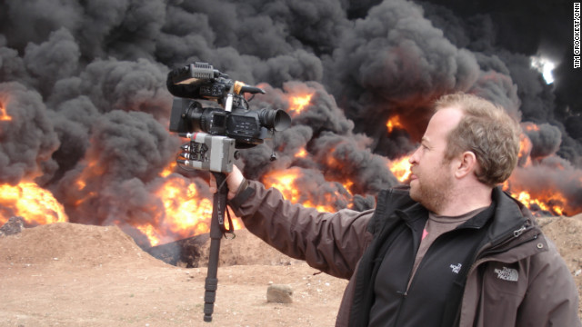 CNN senior photojournalist Neil Hallsworth films an oil fire in Homs, Syria.