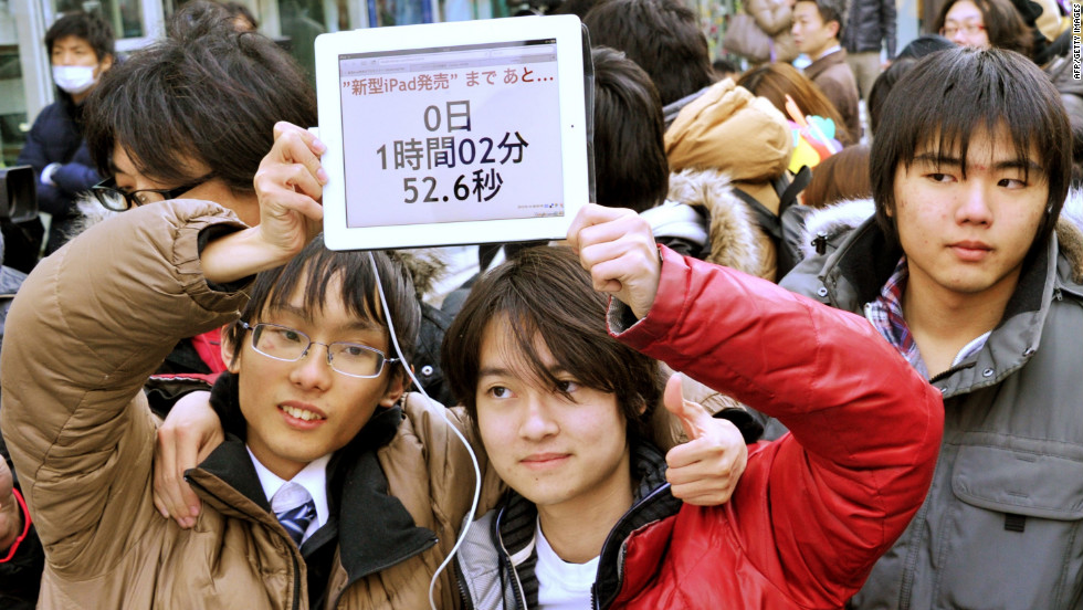 Two Apple fans hold aloft a countdown clock as they wait in line for a new iPad outside the Apple Store in Tokyo, Japan.