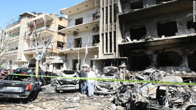 Syrian security officers inspect the scene at a destroyed building following twin bomb attacks in Damascus on Saturday.