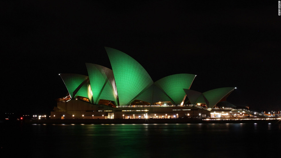 In Australia, the Sydney Opera House is illuminated with green lights.