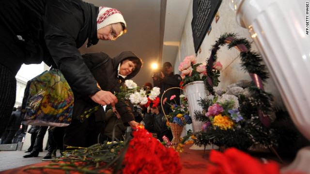 People place candles and lay flowers Friday at a memorial for the victims of last year's subway bombing in Minsk.