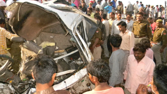 Police and bystanders gather near the mangled wreckage of a van following a collision with a train in India on March 20, 2012.