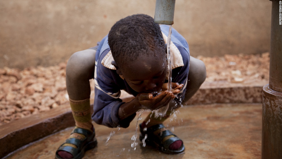 A child plays in clean water from a new handpump in Hambale, Zambia