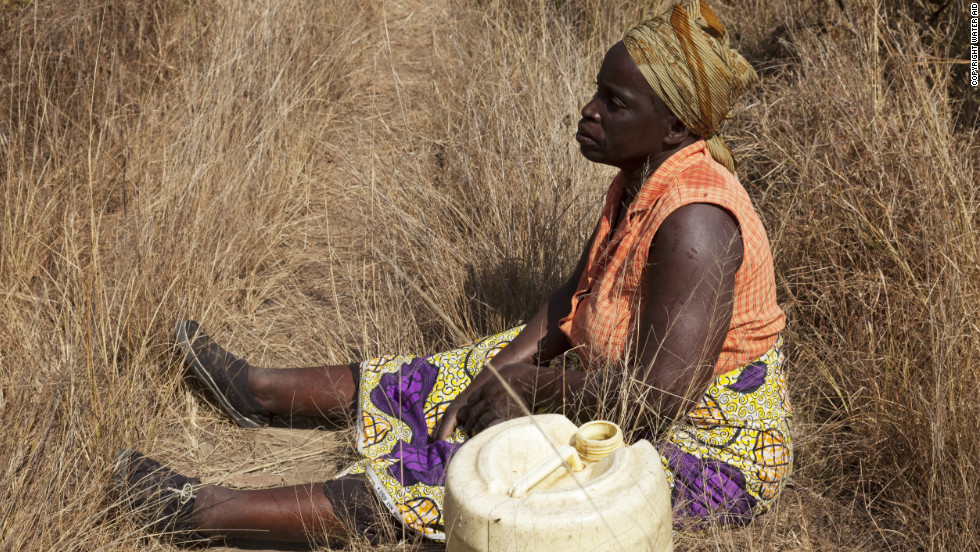 A woman taking a rest on her way home from collecting water near Habeenzu village, Zambia.