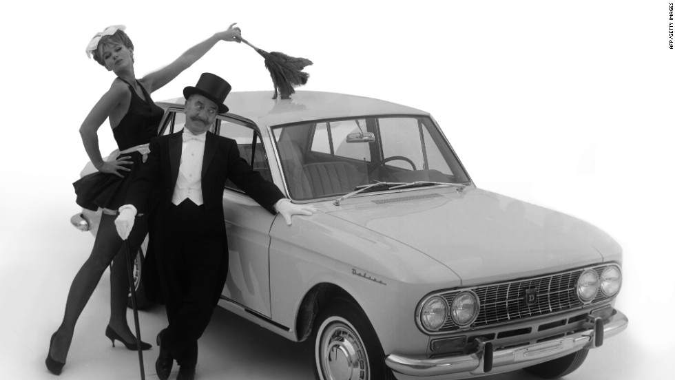 A man stands next to his Datsun  while a woman dressed as a French maid dusts the roof of the vehicle, circa 1966.