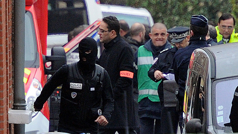 French policemen stand near the apartment of Mohammed Merah on Wednesday. Interior Minister Gueant said the suspect was a French national of Algerian origin.