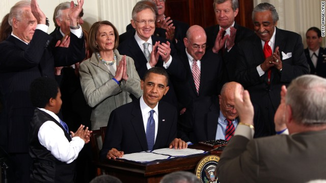 President Barack Obama is applauded after signing the Affordable Care Act at the White House in 2010.