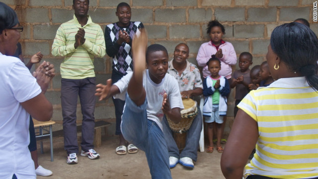 Children dance and sing with a member of Grammy-winning group Ladysmith Black Mambazo.