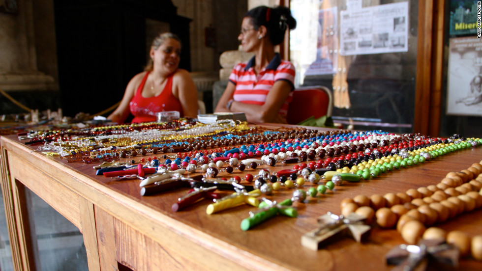 Two women sell crucifixes to tourists.
