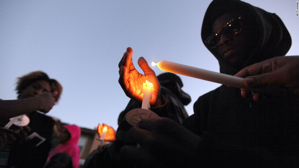 A supporter wears a hoodie during a candlelight vigil Monday at a memorial for Trayvon outside the Retreat at Twin Lakes community where he was shot and killed.