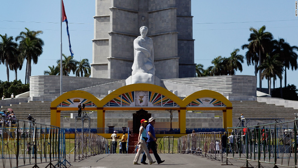 On Saturday, people walk past the stage set up for Pople Benedict XVI in Havana.