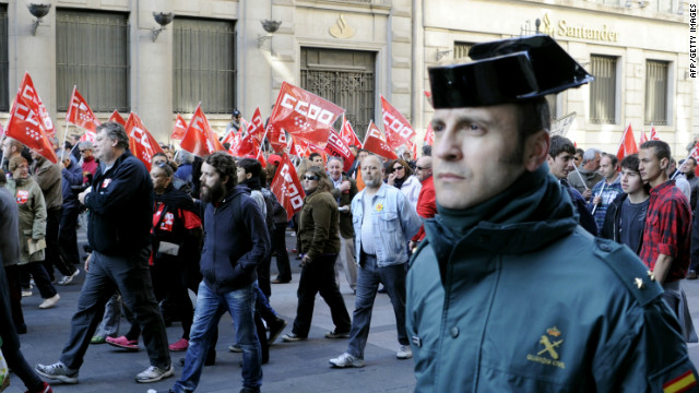 A  police officer walks alongside demonstrators during a day of national strike in central Madrid on Thursday.