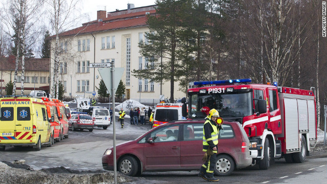 Ambulances, police cars and fire department vehicles are parked outside the school in the Tampere area on Friday.