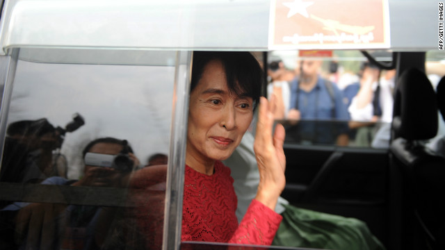 Myanmar opposition leader Aung San Suu Kyi waves to supporters after she visited a polling station in Kawhmu where she stands as a candidate in parliamentary by-elections on April 1, 2012.