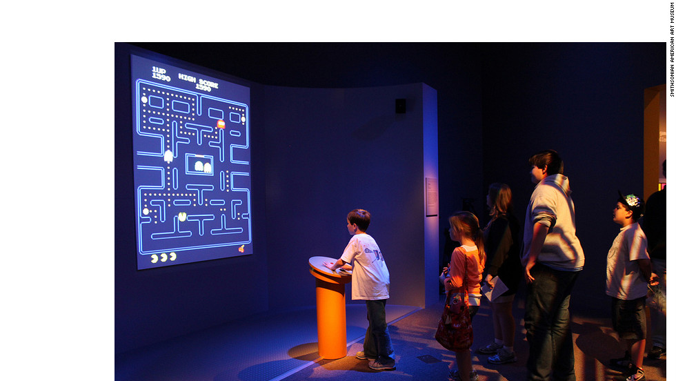 "Kids line up to play a video game that was created before they were born. ""Pac-Man"" is one of five playable games in the exhibit -- ""Super Mario Brothers,"" ""Myst,"" ""Flower"" and ""The Secret of Monkey Island"" are the others."