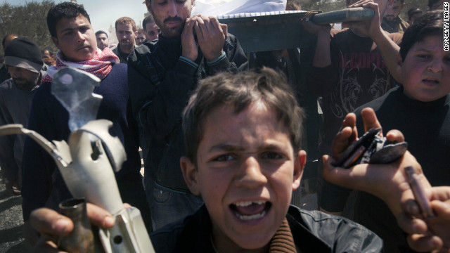 Mourners carry the coffin of Ahmad Qarush, 13, who was killed in Shermin. A boy holds up remains of Syrian Army shells.