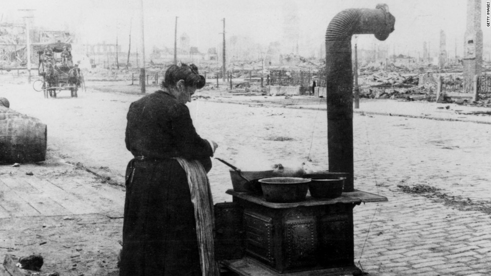 A woman cooks a meal in the street after the San Francisco earthquake on January 1, 1906.