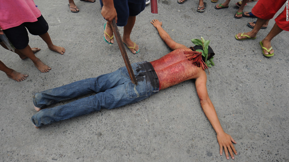 A penitent lies on the ground on the eve of the Good Friday re-enactments of the crucifixion of Jesus Christ in San Fernando City, north of Manila, Philippines. Despite the church's advice to shun the practice, devout Filipinos have themselves nailed to crosses as Asia's bastion of Catholicism marks Good Friday.