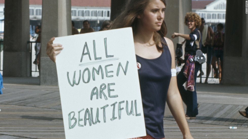 <strong>All women are beautiful: A protest against the Miss America Pageant at Atlantic City, New Jersey, September 6,1969:</strong> A woman walks past with a sign reading 'All women are beautiful'.