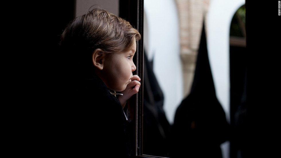 From a window, a child watches penitents of the Dolores brotherhood before a procession Friday during Holy Week.
